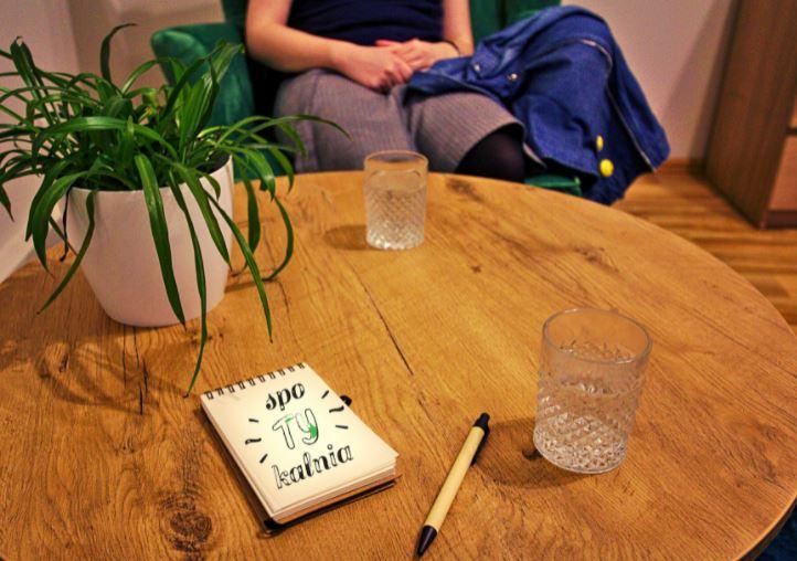 Zdjęcie przedstawia wnętrze Spotykalni, darmowej poradni psychologicznej. Na pierwszych planie okrągły stolik na którym leży notes z napisem Spotykalnia. Na drugim planie dziewczyna widoczna do ramion ze złożonymi dłońmi.